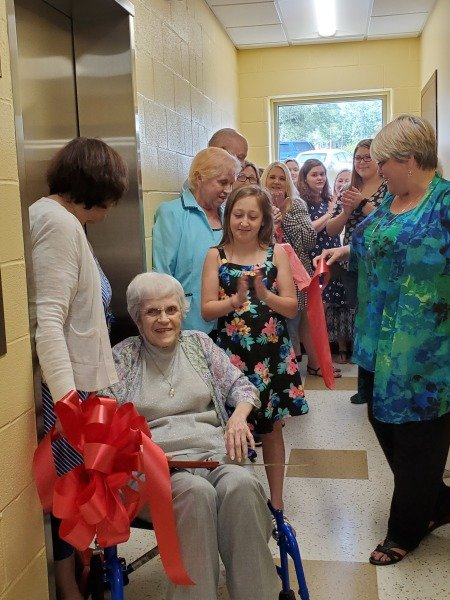 Blanche Trimble cuts the ribbon to the new elevators with help from former WBHML Board Member Kathy Grace.