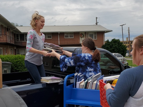 Our student assistants Danni, Abbie, and Eternity unload donated books.