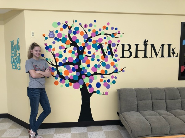 Resident artist Danni poses with the beautiful mural she painted.